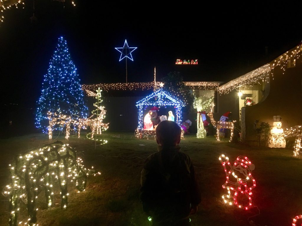 Toddler looking at house Christmas lights